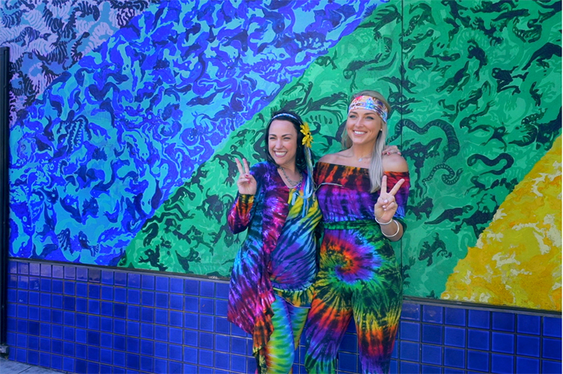 Two women in 1960s tie-dye clothing.