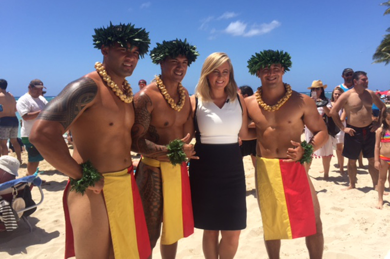 Samantha Armytage with Hawaiian men in traditional costume on the beach at Waikiki.