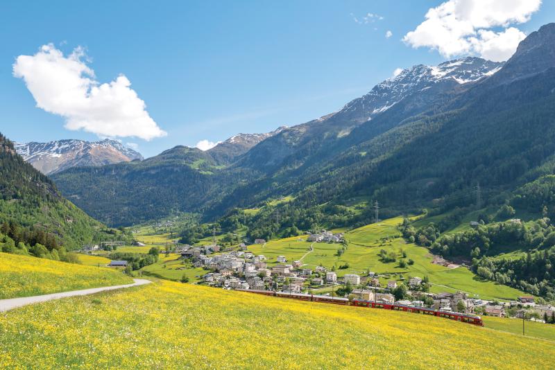Bernina Express traverses Poschiavo Valley in spring.