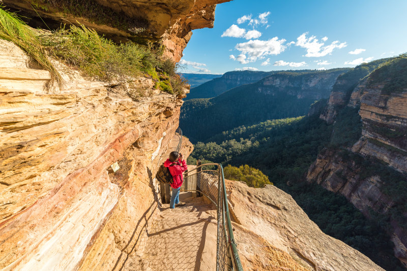 A hiker takes a photo on a trail that skirts sandstone bluffs in New South Wales' Blue Mountains.