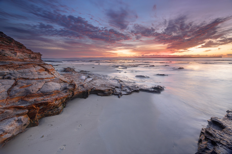 Sunrise over sand, sea and rocks at Jervis Bay, New South Wales.