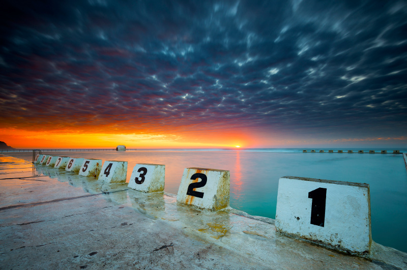 A low-angle view from the corner of Newcastle's Merewether Ocean Baths, as the sun rises over the sea in the background.