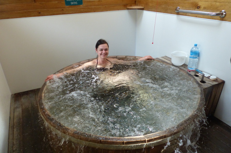 A woman sits in an overflowing round tub full of soda water from natural hot springs.