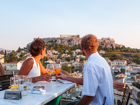 Couple drinking with view of Acropolis