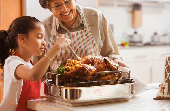 A grandmother and granddaughter cooking a Thanksgiving turkey