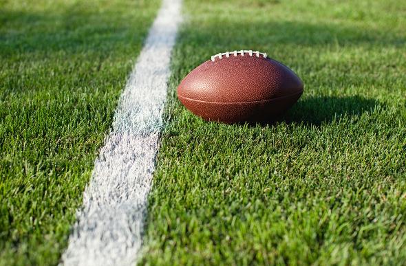 A football sitting on a football field yard line