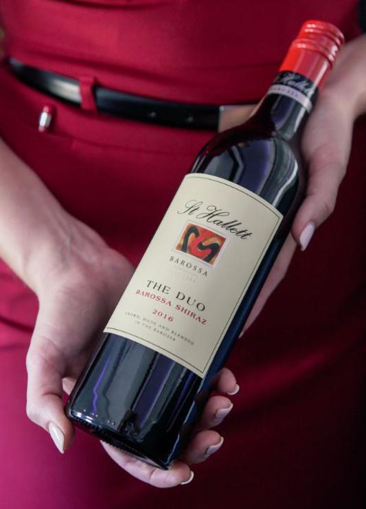 A Virgin Australia flight attendant holding a bottle of wine