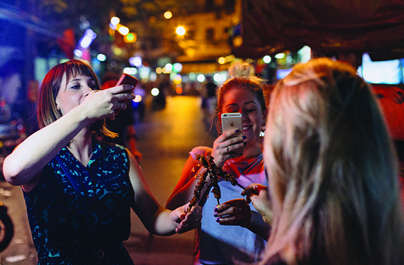 group takes photos of street food in ho chi minh city