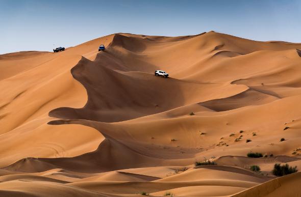 Four-wheel-drives zoom down dunes in the Dubai desert.