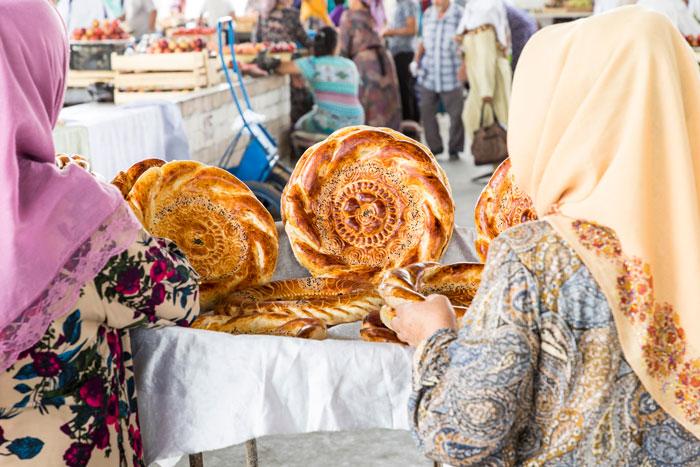 women inspect fresh baked bread in Uzbekistan