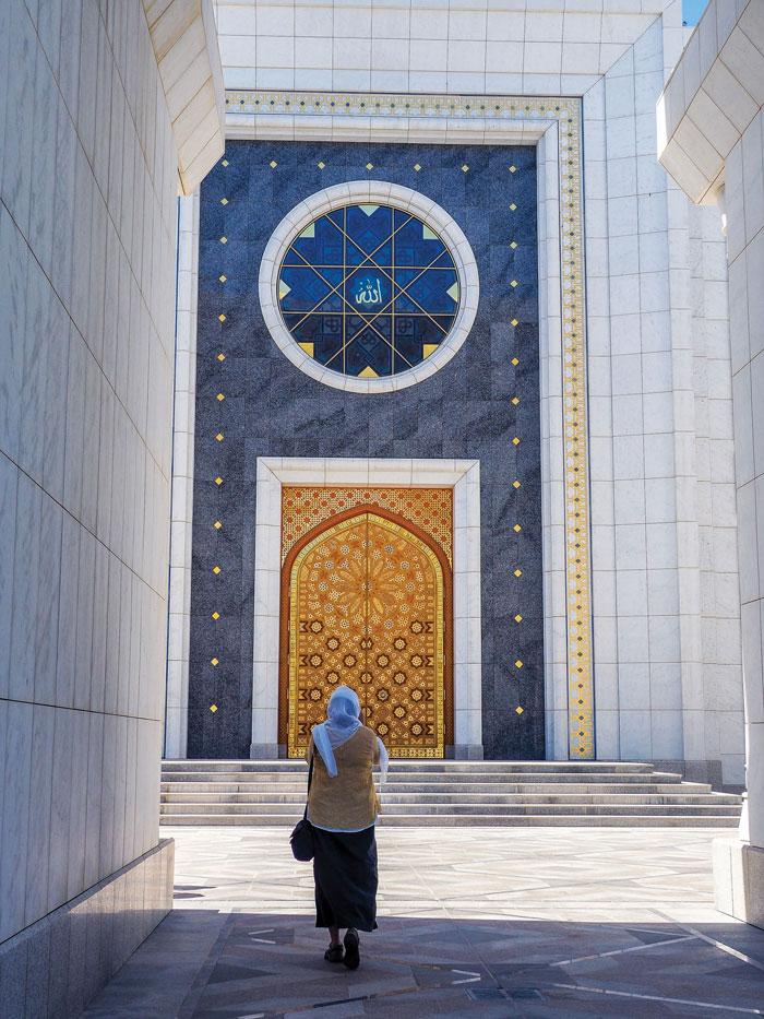 a woman walks to the door of Turkmenbashi Ruhy Mosque