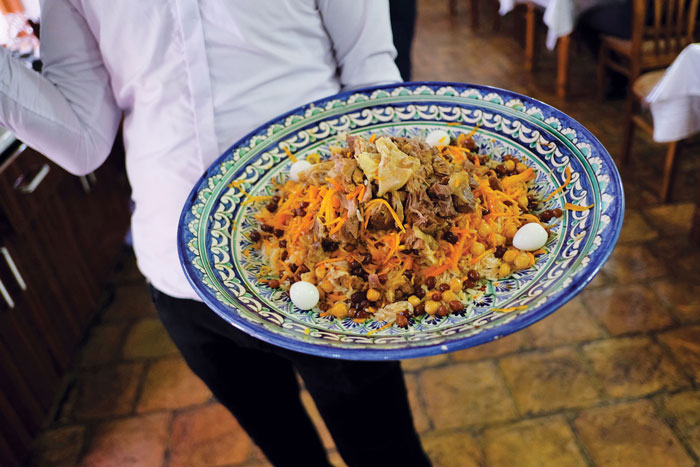 a waiter carries a plate of plov, a combination of lamb, rice, onion and carrots