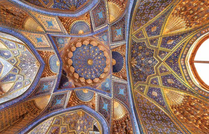 image of the ceiling of intricate detail of the colourful blue and gold ceiling of the Tilya Kori Madrassa in Samarkand
