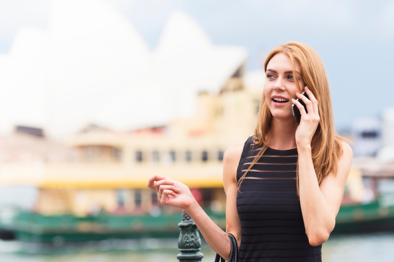 A young woman on the phone outside the Sydney Opera House.