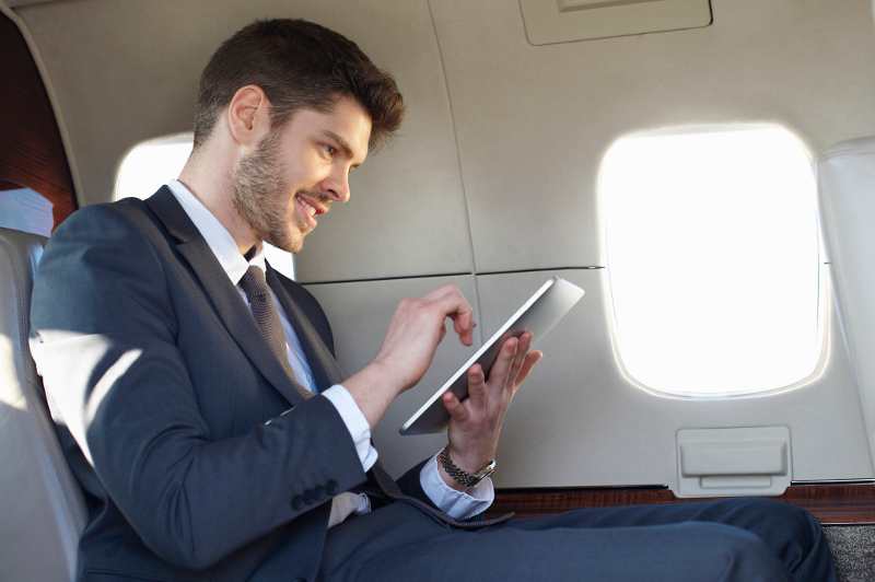 A young businessman uses a tablet on a plane.