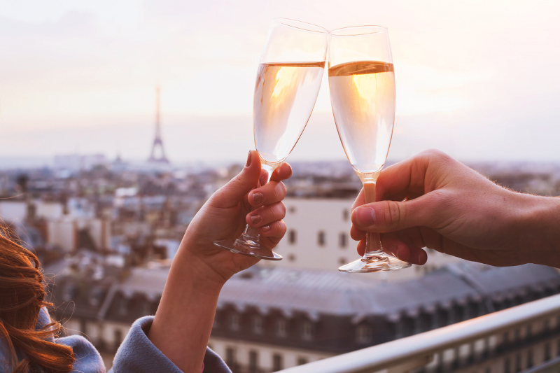A couple of glasses of Champagne being clinked with the Eiffel Tower in the background.