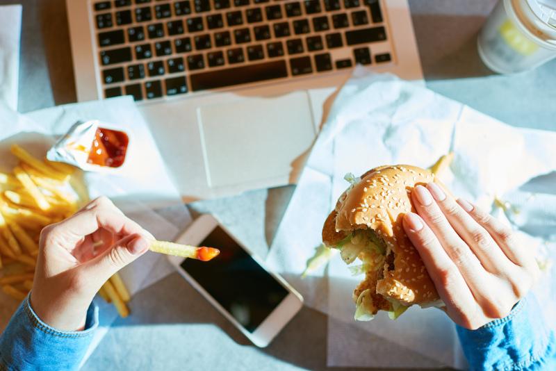 A woman eating a burger and fries while working
