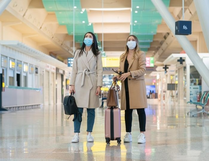 two people in airport with masks looking up