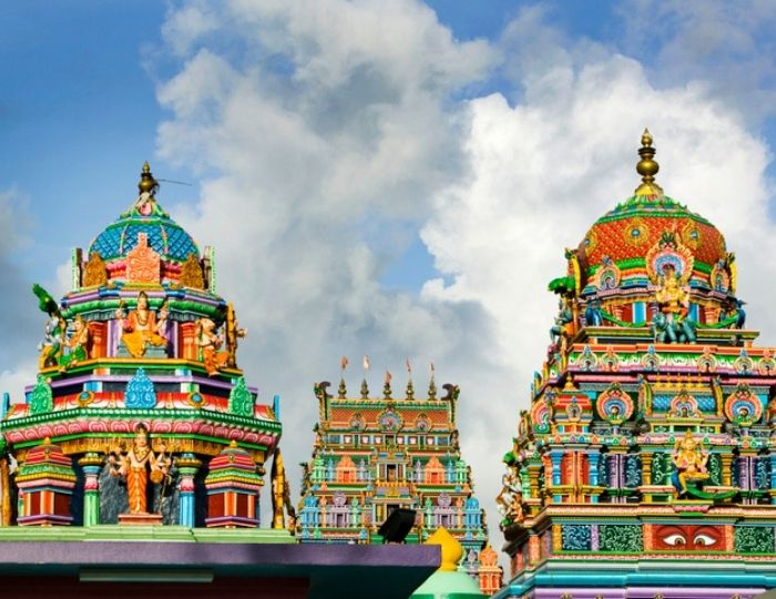 colourful Hindu temple with blue sky and white and grey clouds in background
