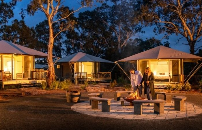 couple near fire with safari tents behind them