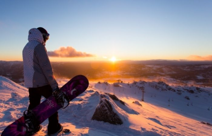Snow boarder watching Sunrise in Blue Cow, Perisher Snowy Mountains.