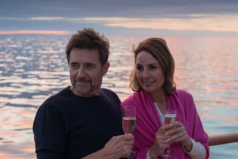 Man and woman holding champagne while leaning on the balcony.