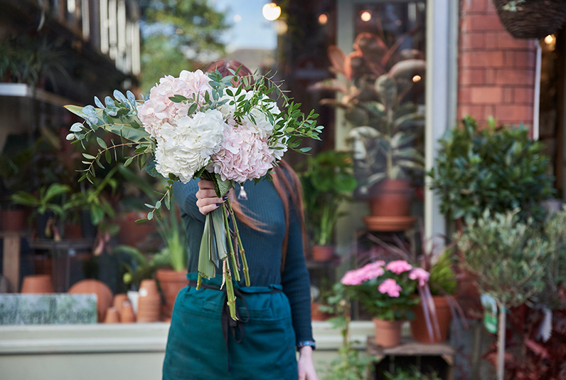 Woman holding bunch of flowers standing outside Northern Flower, Manchester