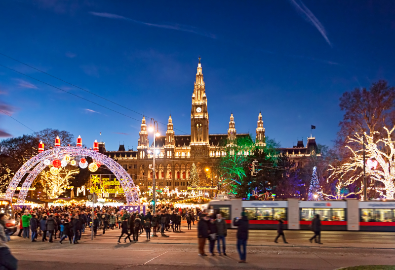 Colourful fairy lights set up with Vienna's town hall in the background lit up at night