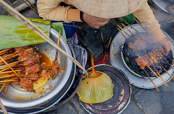 woman sells grilled meat in vietnam