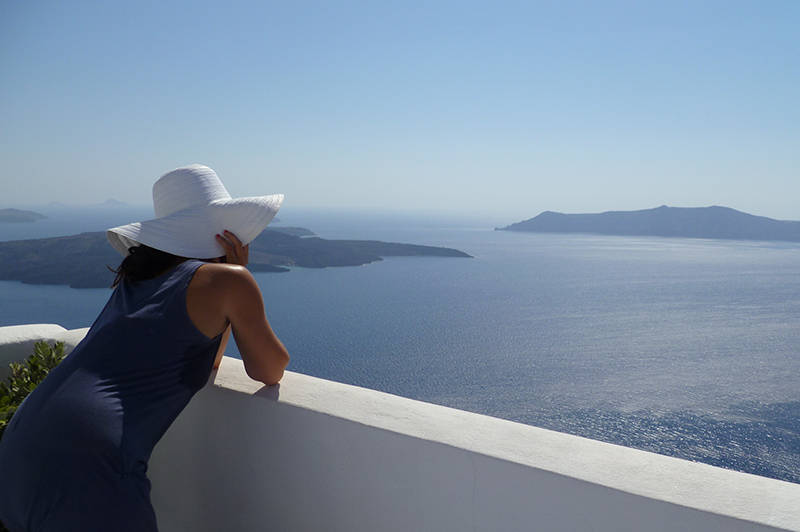 A woman looks at the sea from a Santorini villa.