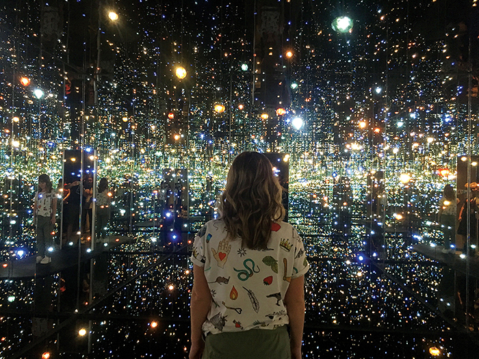 woman looking at Yayoi Kusama's Infinity Mirror