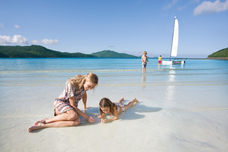 A mother and child play in the shallows of Catseye Beach on Hamilton Island.
