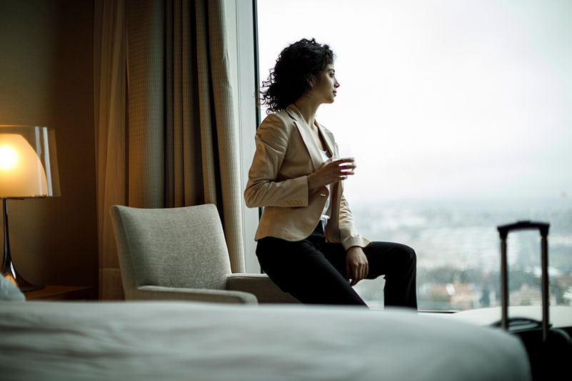 Woman sits in hotel room and looks out window