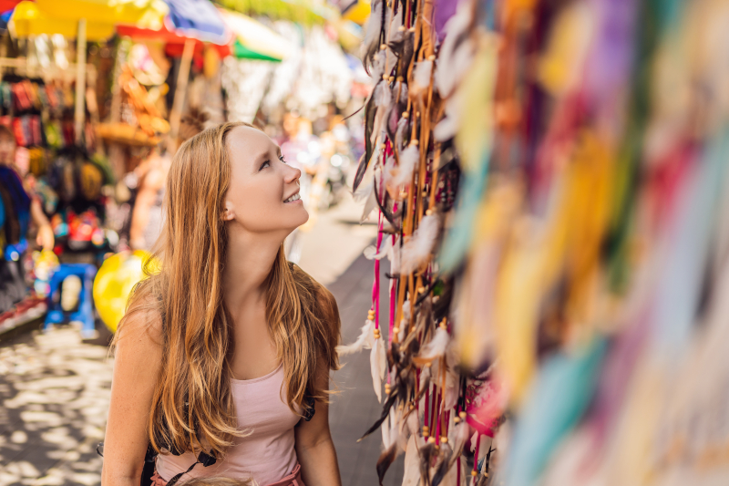 woman gazing up at items hanging in a market