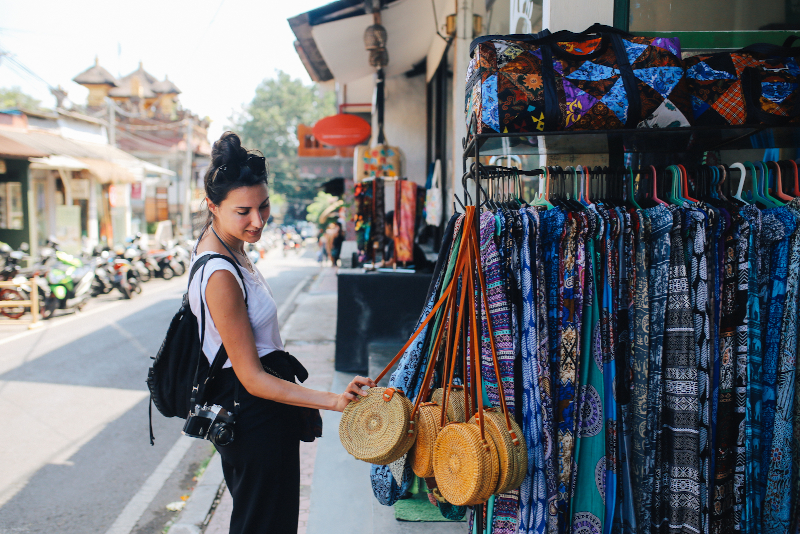 woman at market stall touching a bag