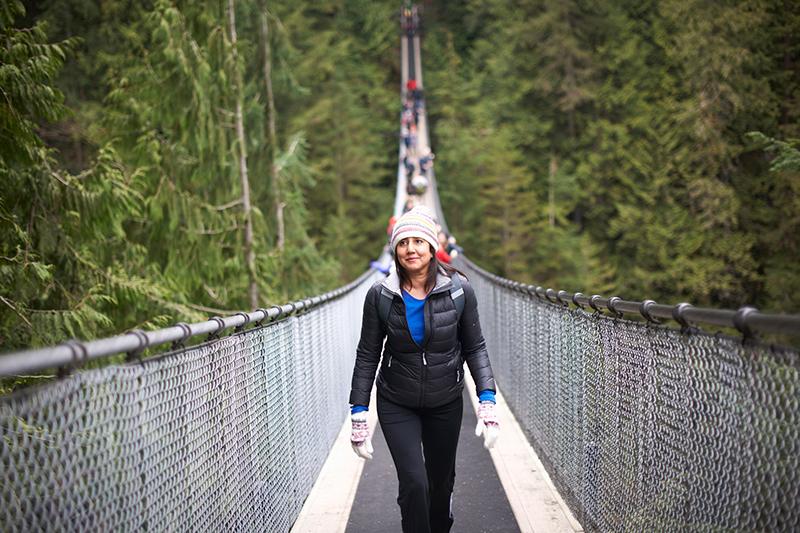 A woman walks on the Capilano Suspension Bridge in Vancouver, Canada.