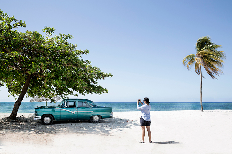 A woman takes a photograph of a vintage car on a beach in Cuba.