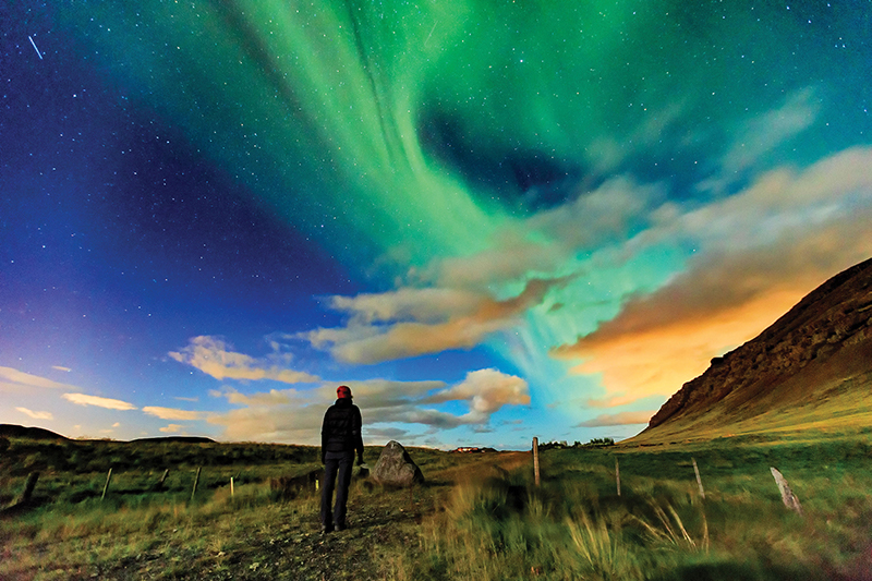 A woman watches the northern lights in Iceland.