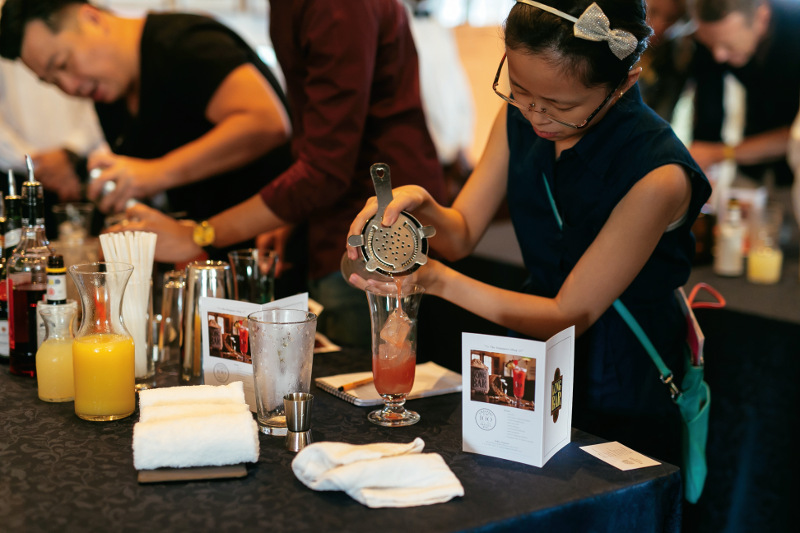 two people making Singapore Sling cocktails