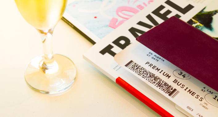 Premium business class boarding pass of frequent flyer with wine glass and passport
